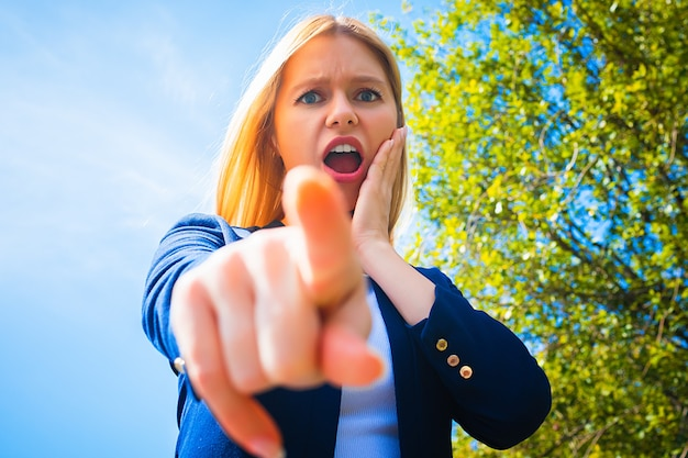 カメラに指を向けて口を開けて怒っている若い女性
