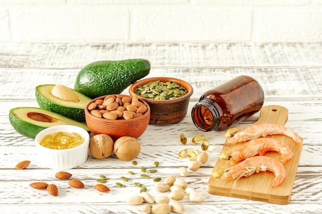 오메가 -3 산의 동물성 및 식물성 공급원. 균형 잡힌 식단 개념입니다. 나무 테이블에 건강 식품의 구색,
