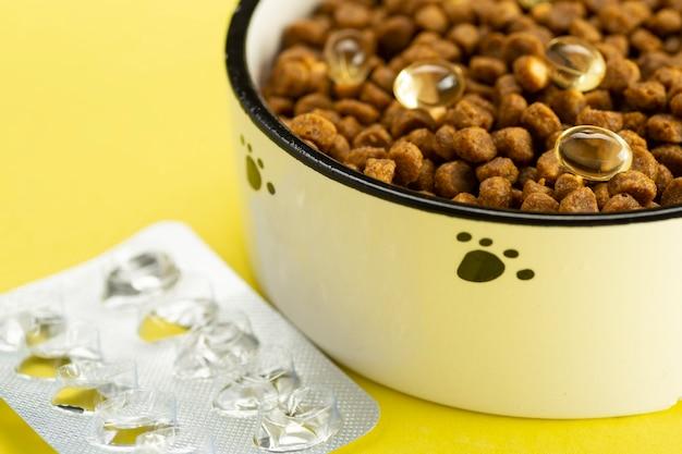 그릇에 정제와 동물 식품