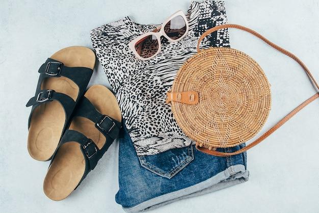 Animal print t-shirt, blue denim shorts, fashionable rattan bag, sunglasses.