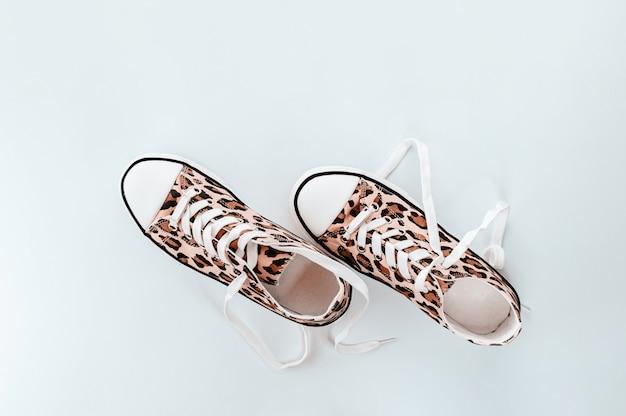 Модные белые кроссовки с принтом животных на светло-сером фоне