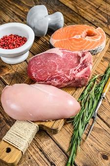 動物性タンパク質は、肉、魚、家禽を調達します。生ステーキ。木製のテーブル。上面図。