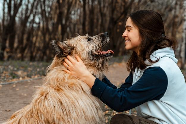 動物の訓練。ボランティアの少女が動物保護施設の犬と一緒に歩きます。秋の公園で犬と少女。犬と一緒に歩きます。動物の世話。