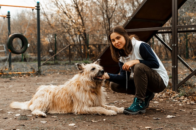 Animal training. a volunteer girl walks with a dog from an animal shelter. girl with a dog in the autumn park. walk with the dog. caring for the animals.