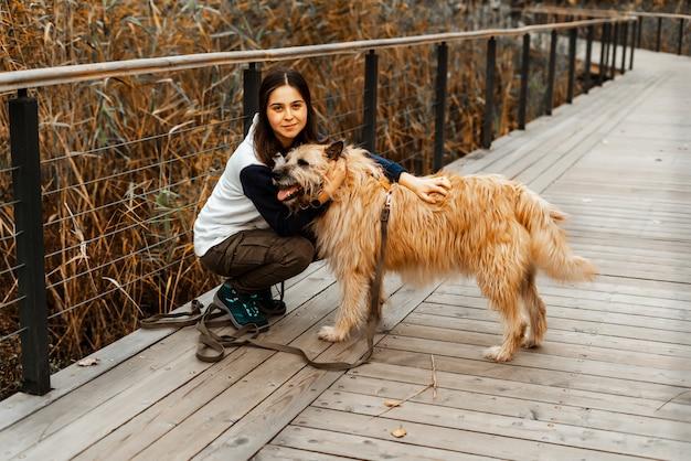Animal training. a volunteer girl walks with a dog from an animal shelter. girl with a dog in the autumn park