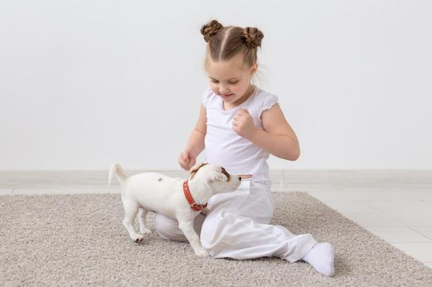 動物、子供、ペットのコンセプト-かわいい子犬と一緒に床に座って遊んでいる小さな子供の女の子。