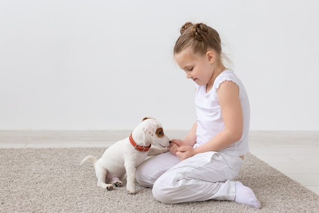 Animals, children and pets concept - little child girl sitting on the floor with cute puppy and playing.