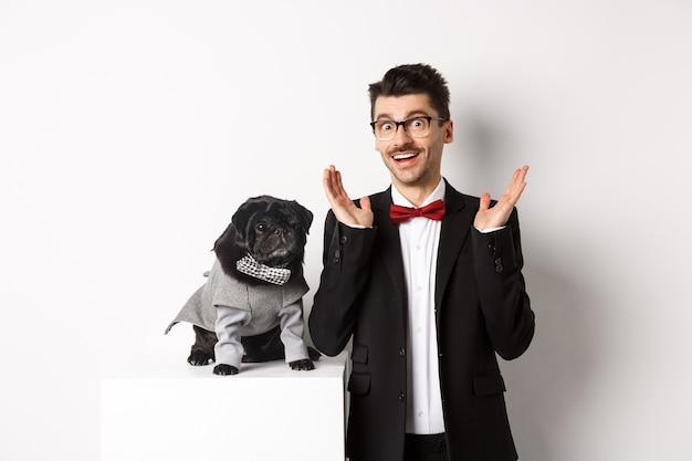 동물, 파티 및 축하 개념입니다. 잘생긴 남자와 의상을 입은 귀여운 강아지가 카메라를 쳐다보며 놀라고 흰색 배경을 제공하는 프로모션에 반응합니다.