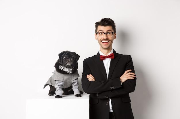動物、パーティー、お祝いのコンセプト。スーツを着た幸せな犬の飼い主と衣装を着た子犬がカメラに興奮している、楽しんで、白い背景の上に立っている