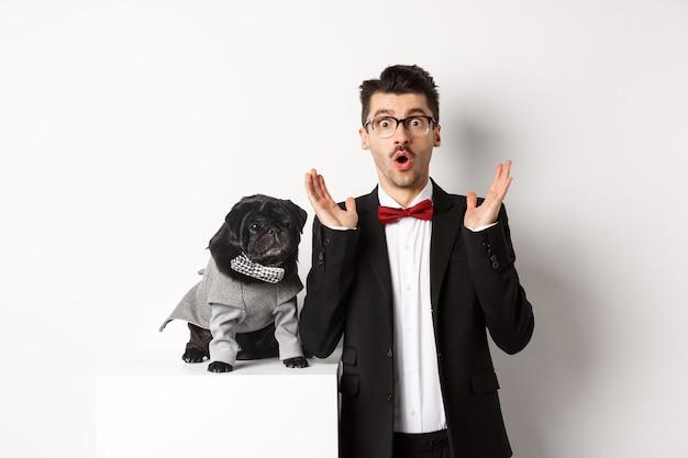 동물, 파티 및 축하 개념입니다. 개 주인과 의상을 입은 귀여운 퍼그가 카메라를 쳐다보며 프로모션 제안에 반응하는 이미지, 흰색 배경