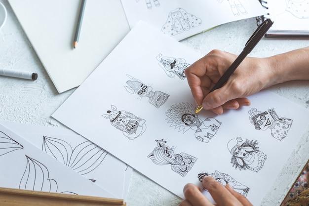 Аниматор дизайнер рисует эскизы различных персонажей.
