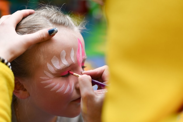 Animator draws a girl drawing on the face at a party