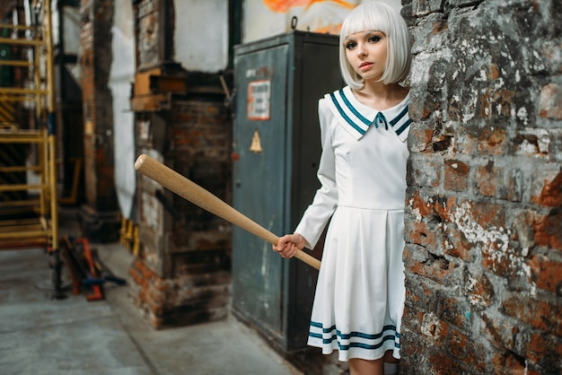 Anime girl with baseball bat. cosplay fashion, asian culture, doll in uniform, cute woman with makeup in abandoned factory shop