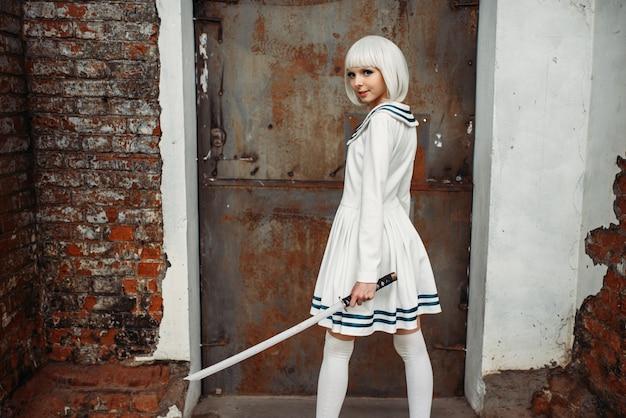Девушка аниме с мечом позирует на заброшенной фабрике