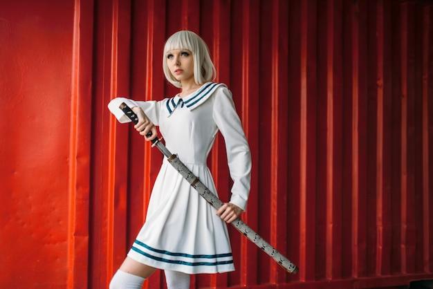 Блондинка в стиле аниме с мечом против красного контейнера. косплей женщина, японская культура, кукла с лезвием