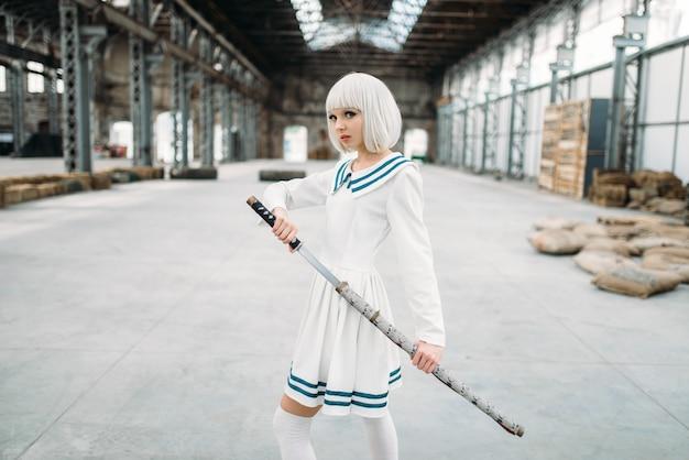 Блондинка в стиле аниме с мечом. косплей женщина, японская культура, кукла с лезвием на заброшенной фабрике