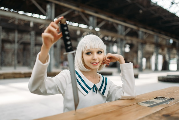 Anime style blonde lady with cold face looks at the sword. cosplay fashion, asian culture, doll with blade, cute woman with makeup in the factory shop