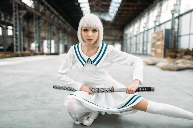 Блондинка в стиле аниме с мечом. косплей мода, японская культура, кукла с лезвием на заброшенной фабрике
