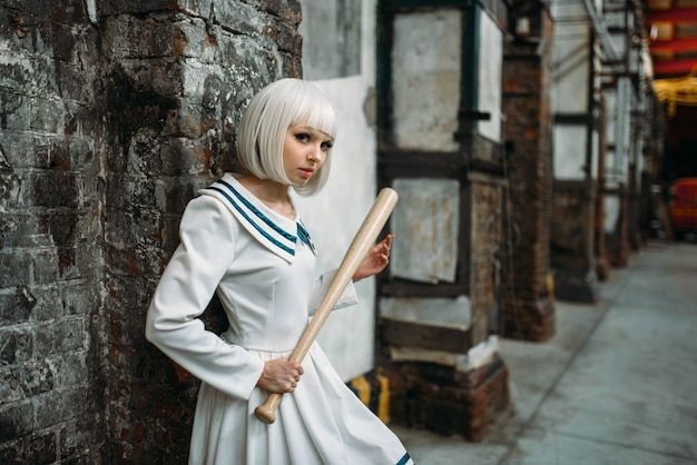 Anime style girl with baseball bat, lolita. cosplay fashion, asian culture, manga doll in uniform, cute woman with makeup in abandoned factory shop