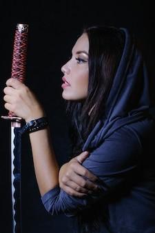 Стилизованная в стиле аниме брюнетка с длинными волосами, суровым взглядом смотрящая на нее с мечом катана