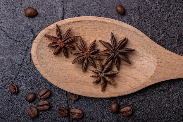 コーヒーの粒とコンクリートの背景に木のスプーンでアニス
