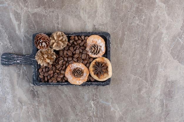 Anice, biscotti, chicchi di caffè e pigne su marmo.
