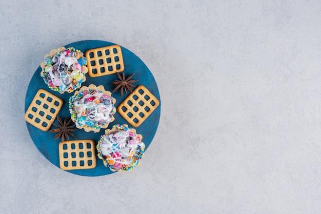 大理石のテーブルの上のボード上のアニス、クラッカー、キャンディーカップケーキ。