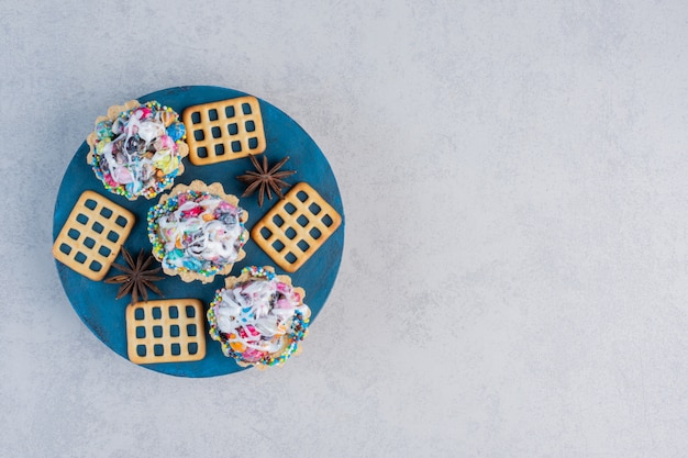Anise, crackers and candy cupcakes on a board on marble table.