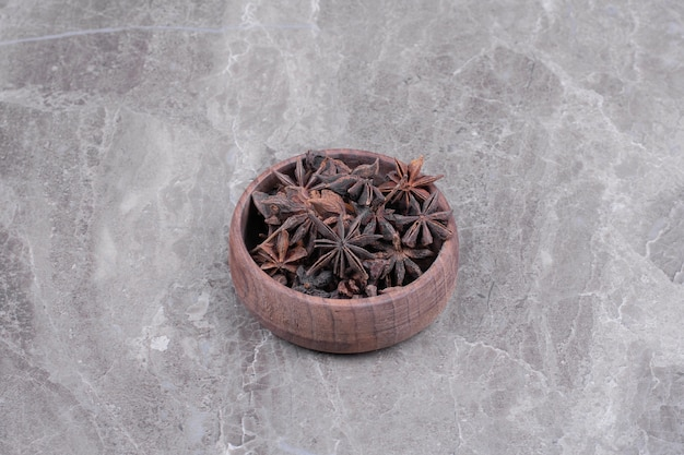 Anise flowers in a wooden cup on the marble
