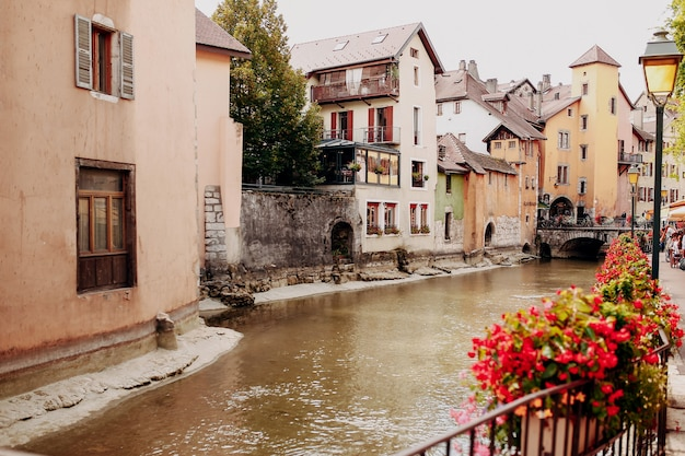 Annecy city water channel with red flowers and old buildings. high quality photo