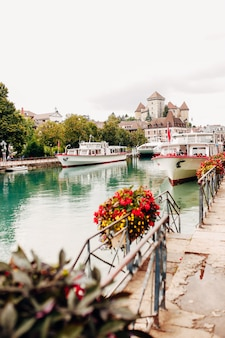 Annecy lake water channel bay with red flowers view to marina from annecy city. high quality photo