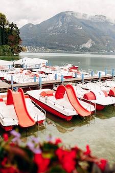 Залив водного канала озера анси с видом красных цветов на пристань из города анси. фото высокого качества