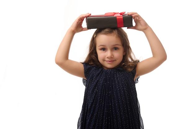 Юбилей и концепция черная пятница. изолированные портрет на белом фоне, копией пространства улыбается маленькая девочка в вечернем платье, держа черную подарочную коробку с красной лентой на ее голове, глядя на камеру.