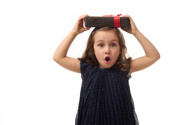 Юбилей, концепция черная пятница. изолированный портрет на белом фоне, копией пространства удивленной маленькой девочки в вечернем платье, держащей черную подарочную коробку с красной лентой на голове, глядя на камеру