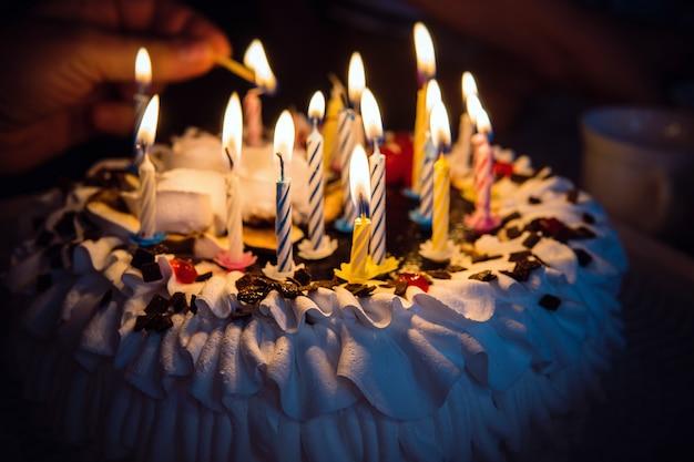 어둠 속에서 손으로 촛불을 태우는 기념일 케이크. 성냥을 든 손이 생일 케이크의 촛불에 흰색 크림을 얹고 있습니다. 케이크에 16개의 초 16개.