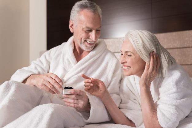 기념일 반지. 침대에 누워 행복을 표현하면서 아내에게 반지를주는 즐거운 미소 세 남자