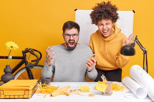 怒っている怒っている同僚は、デスクトップのオフィスで猛烈な表情のポーズをとっています。何気なく服を着た多くの仕事に大声でうんざりしています。