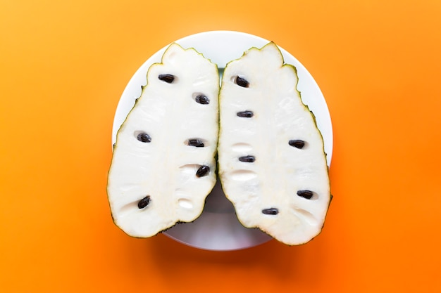 Annona muricata or graviola. soursop fruit, sugar sweet apple, custard milk apple cut in half, two halves of fruit on white plate on yellow orange . top view. exotic tropical asian fruit.