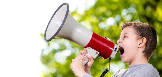 Объявление концепции, мальчик кричит или кричит в мегафон над лесом