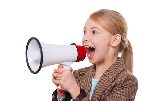 Объявление хороших новостей. веселая маленькая девочка в формальной одежде кричит в мегафон, стоя изолированной на белом