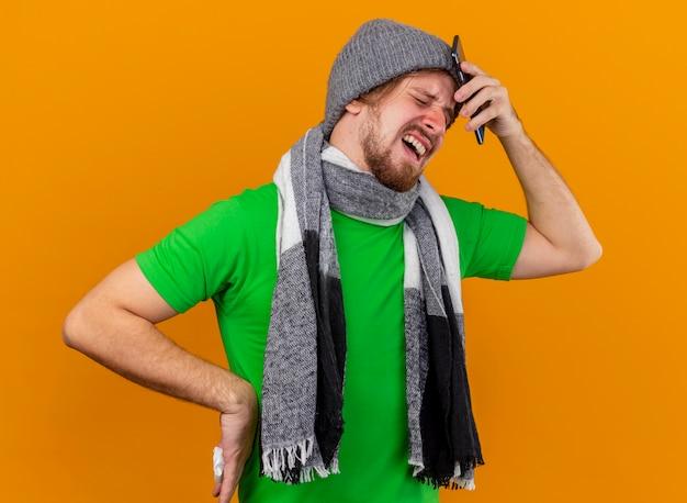 Infastidito e dolorante giovane bello slavo malato che indossa cappello invernale e sciarpa tenendo il telefono cellulare e il tovagliolo tenendo la mano sulla vita toccando la testa con il telefono con gli occhi chiusi