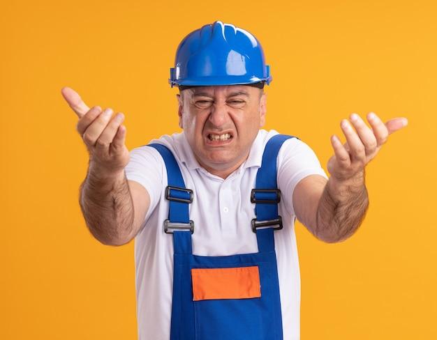 오렌지 벽에 고립 된 두 손으로 앞에 균일 한 포인트에 짜증이 성인 작성기 남자