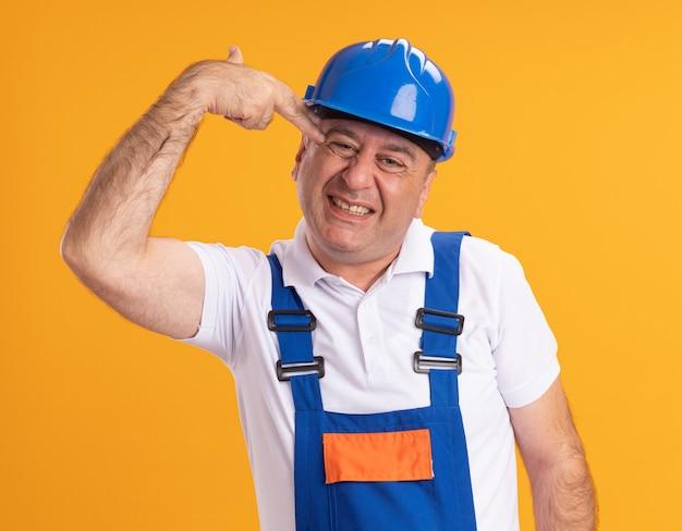 Uomo adulto infastidito del costruttore in segno della mano della pistola di gesti uniformi e tiene al tempio isolato sulla parete arancione