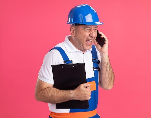 Uomo adulto infastidito costruttore in uniforme tiene appunti e colloqui sul telefono isolato sulla parete rosa