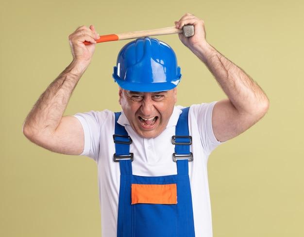 L'uomo adulto infastidito del costruttore in uniforme tiene il martello sopra la testa isolato sulla parete verde oliva
