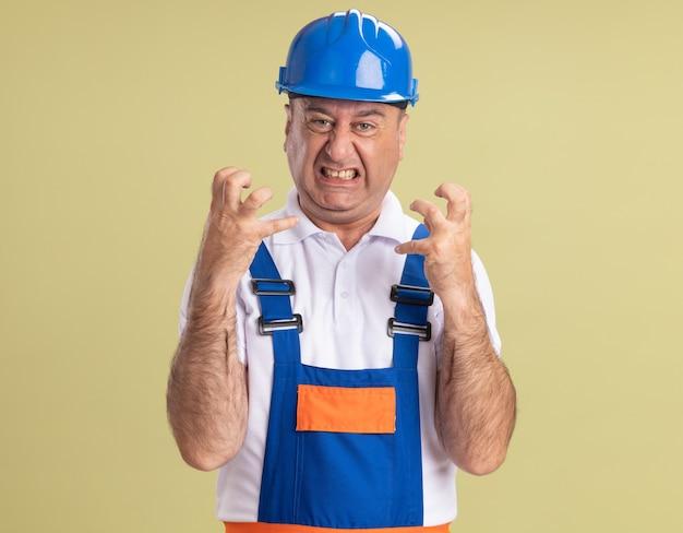 Uomo adulto infastidito costruttore in uniforme stringe le dita isolate sulla parete verde oliva