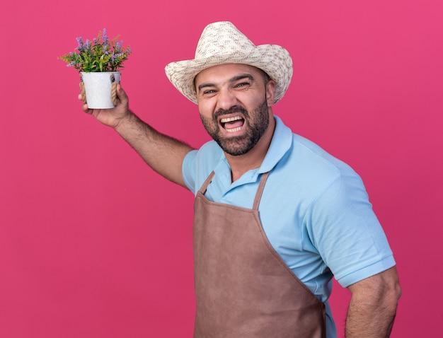 Giardiniere maschio caucasico adulto infastidito che indossa cappello da giardinaggio che tiene vaso di fiori