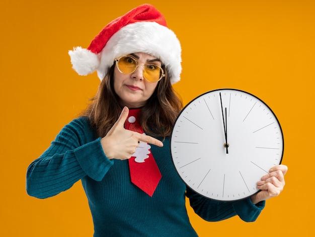 Donna caucasica adulta infastidita in occhiali da sole con cappello da babbo natale e cravatta di babbo natale che tiene e punta all'orologio isolato sulla parete arancione con spazio di copia