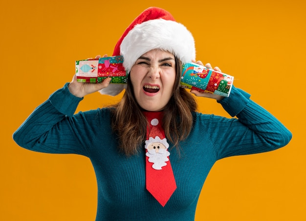 Annoyed adult caucasian woman with santa hat and santa tie holding paper cups close to ears isolated on orange background with copy space