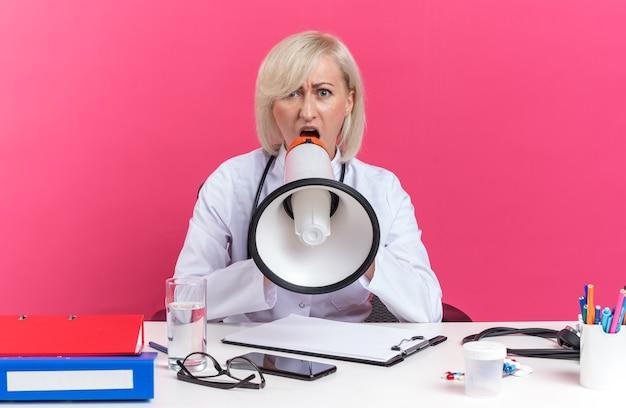 의료용 가운을 입은 성가신 성인 여성 의사가 사무실 도구를 들고 책상에 앉아 카피 공간이 있는 분홍색 벽에 격리된 시끄러운 스피커에 소리를 지르고 있습니다.